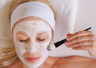 Young beautiful girl applying homemade facial mask i at home.Skin care, beauty treatments.