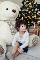 little beautiful girl near Christmas tree and big Teddy bear. Christmas gift