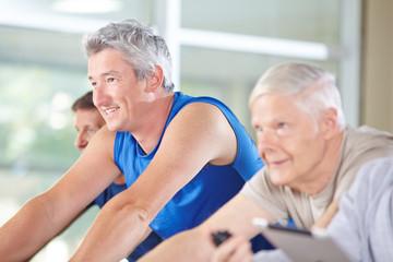 Senioren fahren Fahrrad im Fitnesscenter