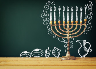 image of jewish holiday Hanukkah with drawing menorah candles (traditional Candelabra), donuts and dreidels (spinning top) over chalkboard background