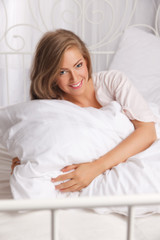 Beautiful smiling woman in the bed