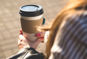 Paper cup with coffee in hand at the girl