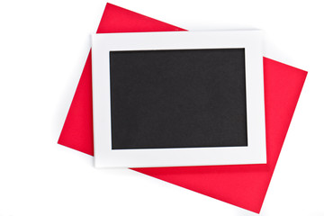 horizontal white photo frame with black field and red paper under angle on white background isolated with real shadows