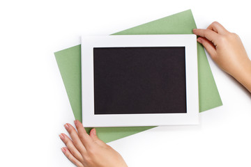 hands holding horizontal white photo frame with black field and green paper under angle on white background isolated with real shadows