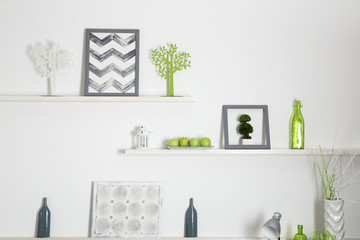Different home objects and decoration on shelves on white wall background