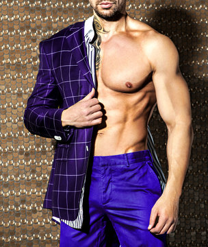 Handsome tattooed man with beautiful muscular body in violet