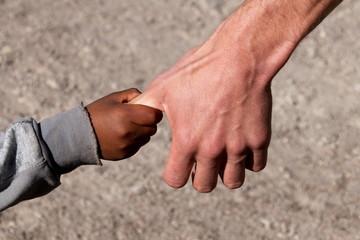 Flüchtlingskind an Hand eines Helfers