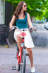 Young happy woman on bike in european city