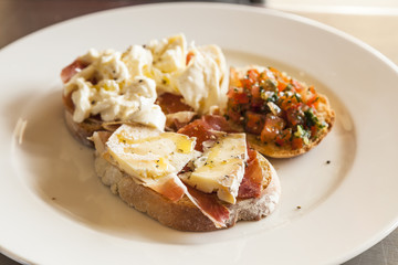 Bruschetta with prosciutto, goat cheese and fried tomatoes