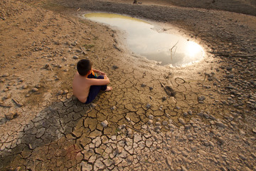 Water crisis, Child sit on cracked earth near drying water.