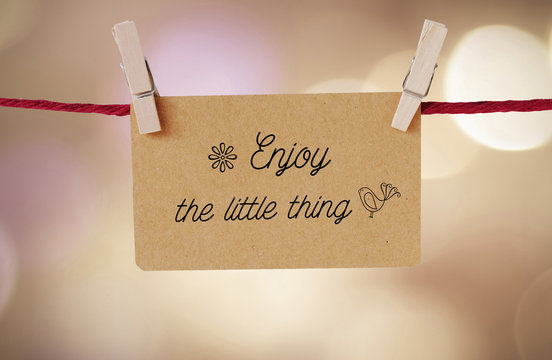 Enjoy the little thing : Quotation on paper card hanging on red