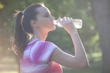 young sporty woman drinks water from a bottle