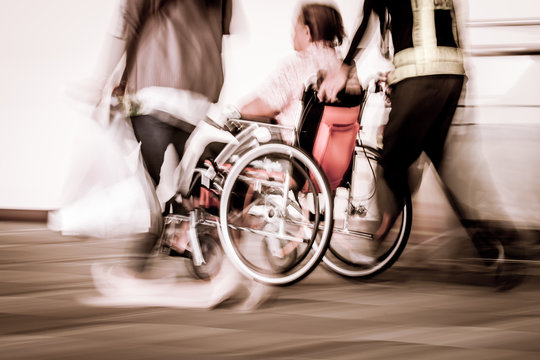 Blur motion of disabled person sit in wheelchair and passengers