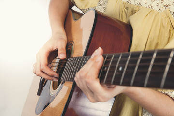 woman's hands playing guitar, close up. Vintage tone