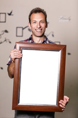 Happy man holding portrait frame