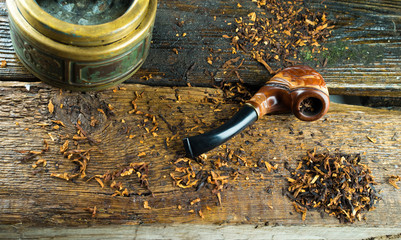 wooden smoking pipe, tobacco and vintage ashtray lie on a wooden table