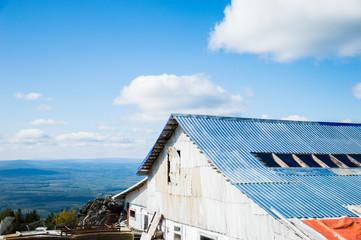 белое Здание с синей крышей на фоне леса