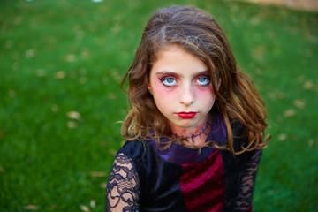 Halloween makeup kid girl blue eyes in outdoor lawn