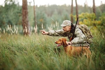 Foto auf Gartenposter Jagd yang Hunter with Rifle and Dog in forest
