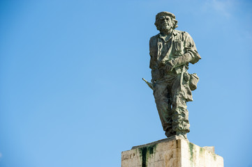 Statue of Cuban revolutionary Che Guevara stands in blue sky at a mausoleum dedicated to him and other fighters from the revolution