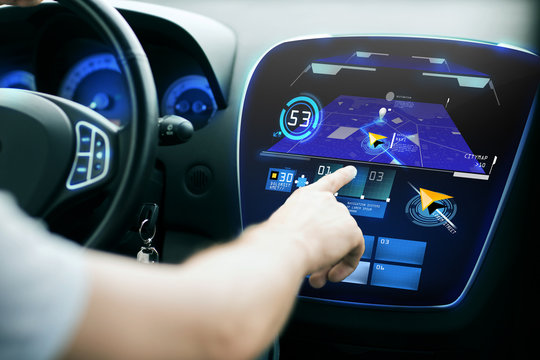 male hand using navigation system on car dashboard