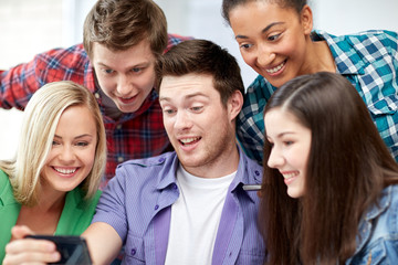 group of happy students with smartphone at school