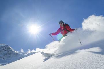 Schnee staubt, Sonne scheint, Skifahrer im Tiefschnee