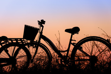 beautiful landscape image with Silhouette Bicycle at sunset in v