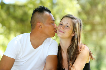 Young mixed couple kissing in a park