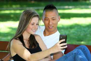 Young mixed couple sitting attacking photograph on a bench in a park