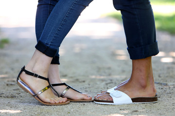Feet of a mixed couple in a park