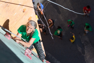 Aged Lady Doing Extreme Sport Elderly Female Moving Up on Outdoor Climbing Wall Sporty Clothing on Fitness Training Intense but Positive Face Using Rope and Belaying Gear