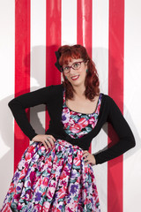 View of pinup young woman in vintage style clothing next to red and white striped tents.