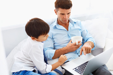 Home education. Father helping son to do homework