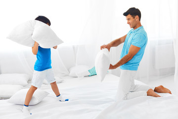Dad and son having fun. Pillow fight.