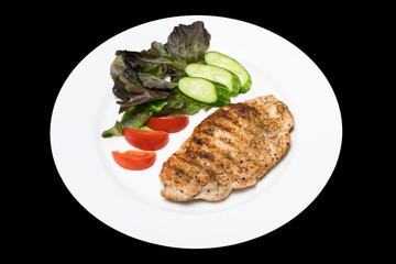 Photo of a chicken stake on a white plate with a cucumber, tomat