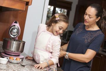 Mamá poniéndole el delantal a la hija para cocinar juntas