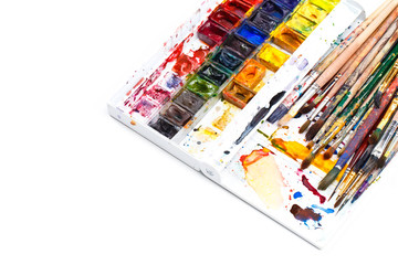 Used water-color paint-box and dirty artist paint brushes. Top view. Isolated image with space for your text