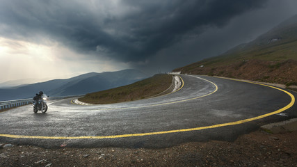 Driving a motorcycle on alpine highway toward the storm