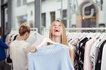 frau freut sich über ein schnäppchen in einer boutique