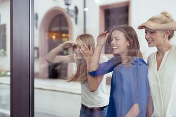 drei freundinnen schauen durch das schaufenster in ein geschäft