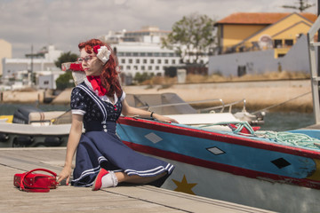 View of pinup young woman in vintage style clothing on a marina.