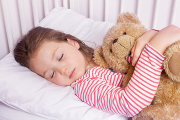 cute little girl sleeping with stuffed toy in her bed
