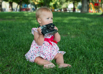 Baby girl is playing with old camera on grass. Baby with camera