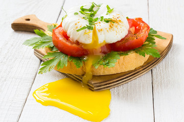 Delicious poached egg with tomato and parsley on toast