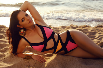 beautiful girl with dark hair in elegant bright bikini posing on beach