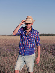 Attractive young man standing in a field. Cowboy