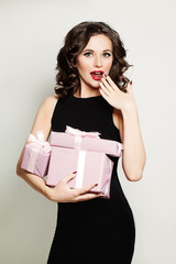 Surprised Woman holding Gift Box. Fashion Model with Open Mouth