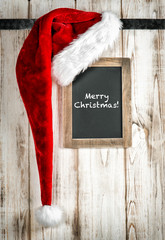 Red Santa hat and vintage chalkboard. Christmas decoration