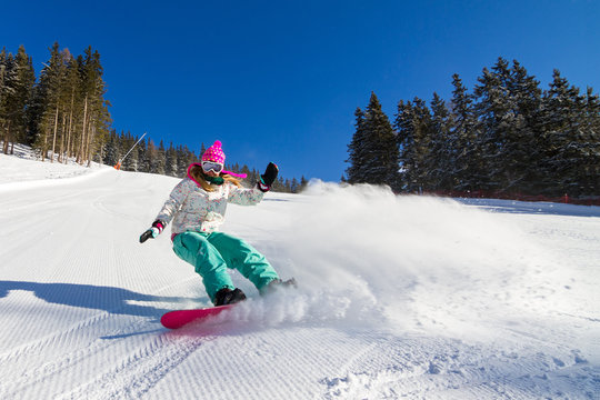 Female snowboarder rocking the slopes on a sunny morning in the Italian alps